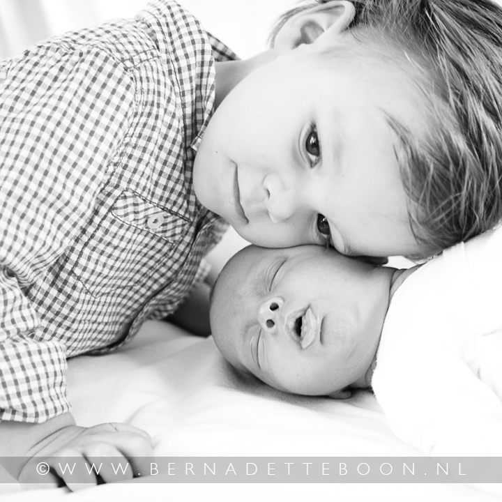 Een foto van een newborn baby met zijn broertje die hem knuffelt. Door Bernadette Boon