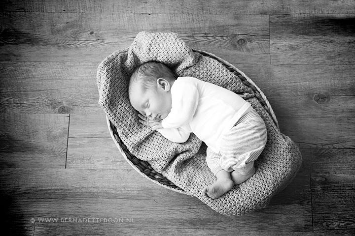 Newborn baby foto van kindje in mandje op houten vloer door Bernadette Boon