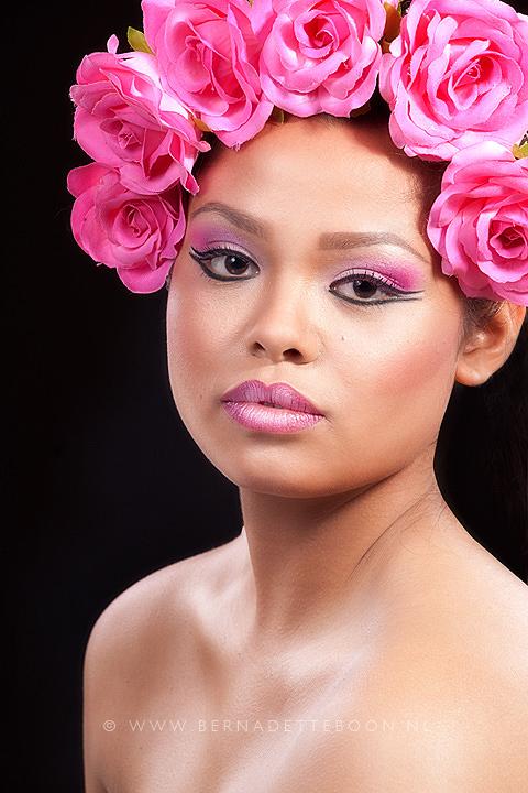 Foto van dame met roze bloemen in het haar.
