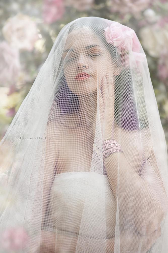 een dromerig portret van jonge dame met sluier en bloemen door Bernadette Boon