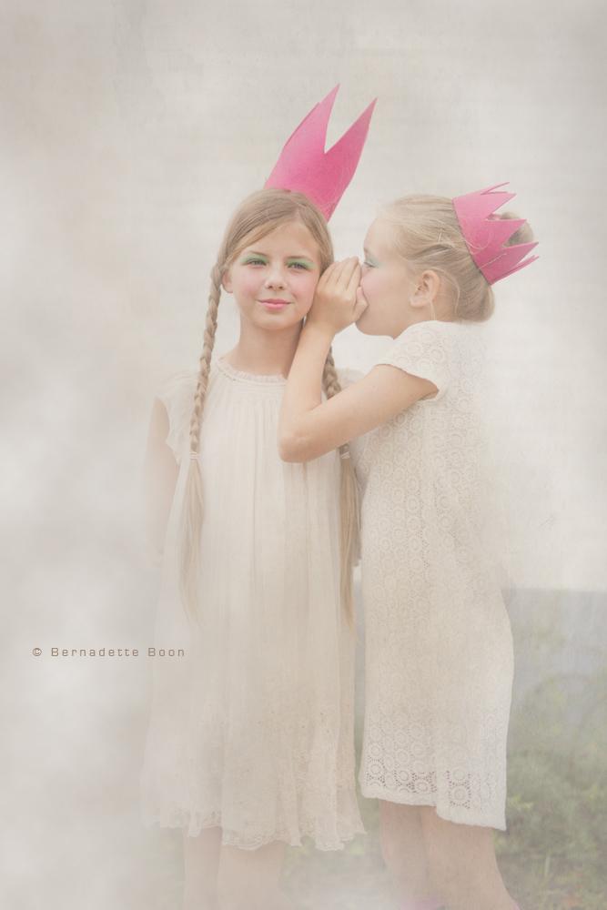 een dromerige foto(bewerking) van 2 meisjes in lichte jurkjes met een roze kroontje