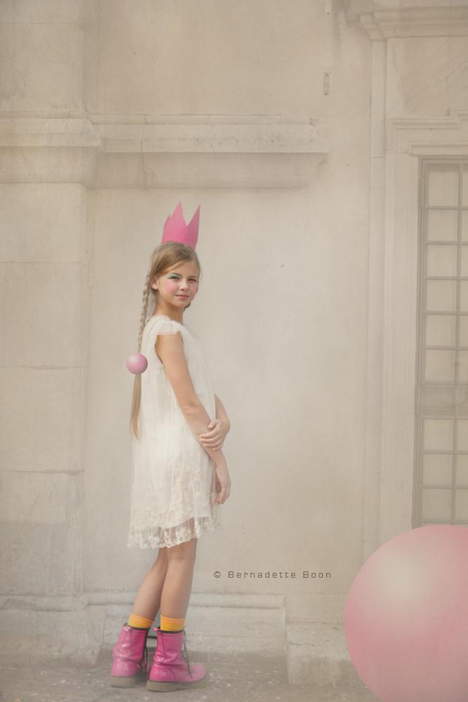 meisje met wit jurkje, roze schoenen en roze kroontje