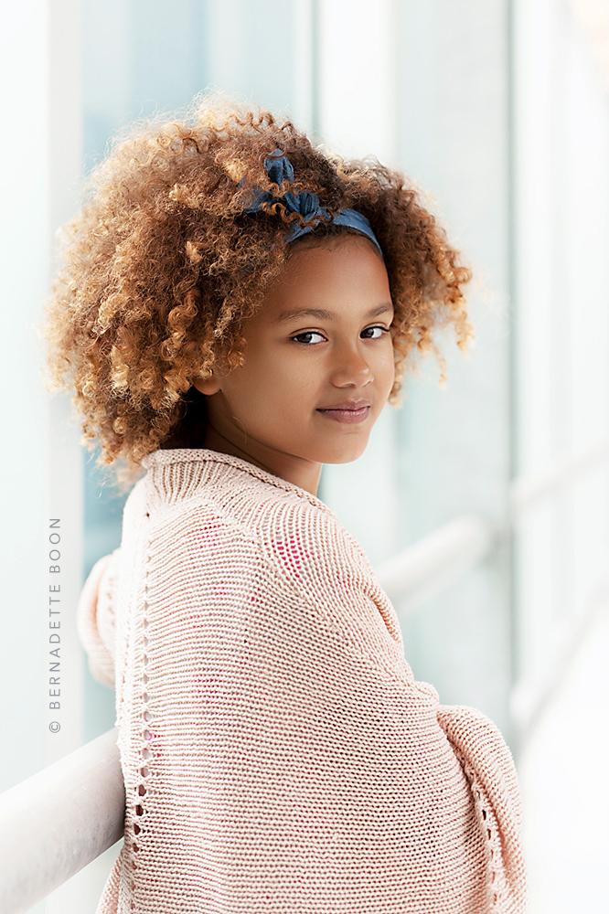 Foto van meisje met lekker krullen en met zachte kleuren