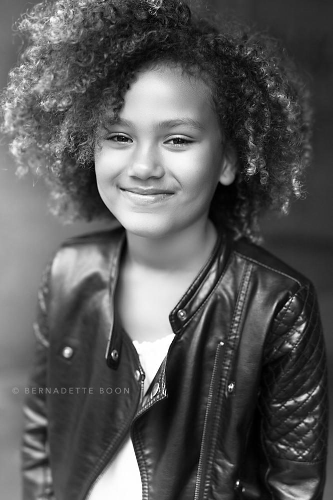 zwart wit foto van meisje met krullen en leren jasje