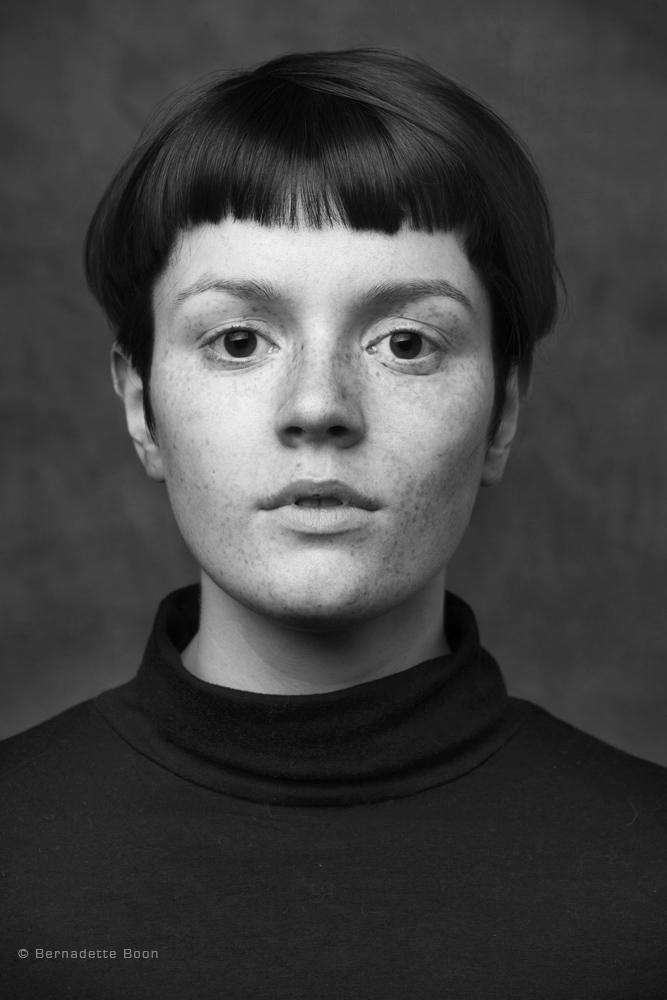 Zwart wit foto van jonge dame met kort stijl haar en sproetjes door Bernadette Boon